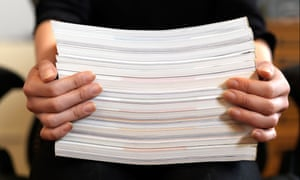 A close up view of female hands holding up a stack of paper