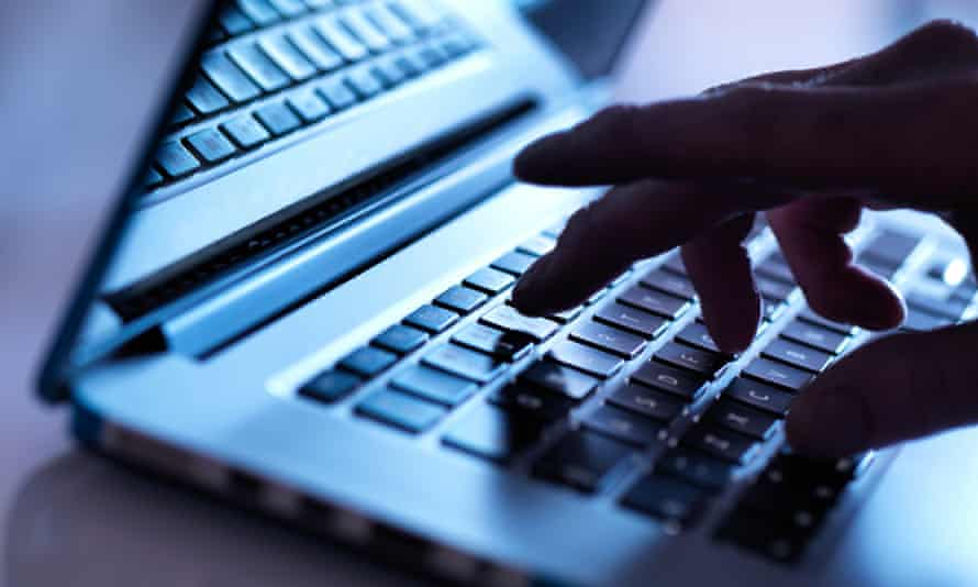 Fingers typing on a laptop computer.