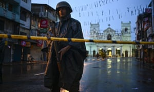 A Sri Lankan soldier stands guard in the rain at St Anthony's shrine in Colombo. Security remains high amid warning further attacks were possible.