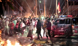 Fire crackers explode near supporters of presidential candidate Prabowo Subianto during clashes with the police in Jakarta on Wednesday
