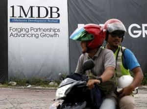 Motorcyclists pass a 1Malaysia Development Berhad (1MDB) billboard at the Tun Razak Exchange development in Kuala Lumpur, Malaysia, February 3, 2016.