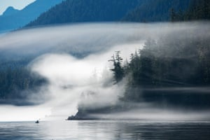 Kayaker in Broughton Archipelago, British Columbia. The Broughton archipelago, in the southern reaches of the rainforest, is an idyllic place for kayaking. As I watched the fog shape-shift from a friend's boat, a group of kayakers appeared. Killer whales, humpbacks and sea lions are also common sights.