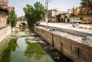 A filthy canal runs past Habib's carpentry workshop