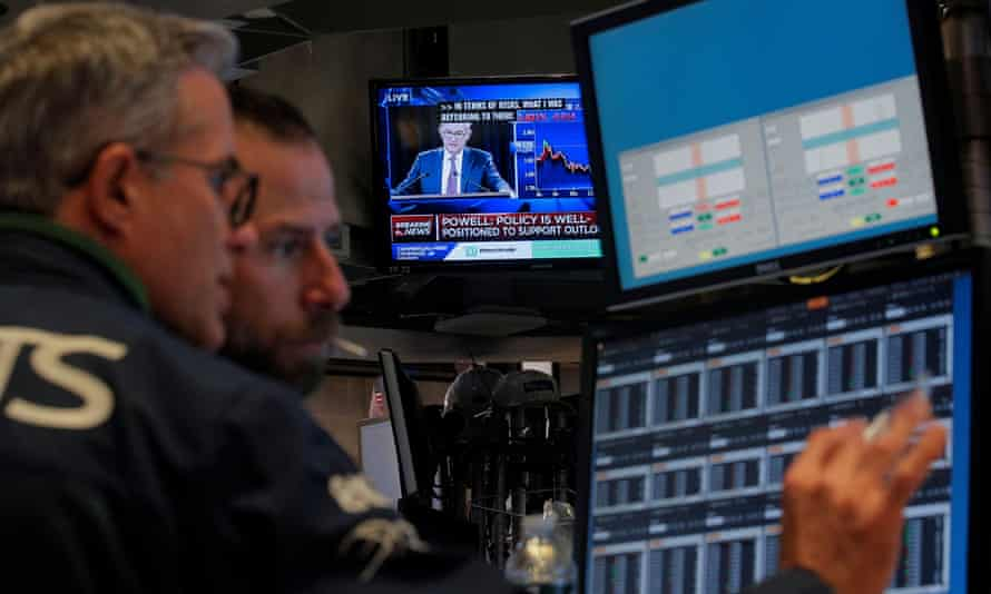 Traders work in the New York stock exchange as a screen shows the Fed chair, Jerome Powell