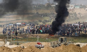 Black smoke rises while Palestinians protest on the Gaza side of the border with Israel.