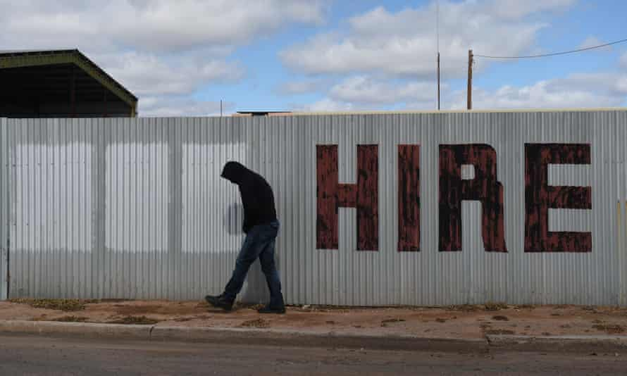 A man walks past a hand painted hire sign in the NSW outback town of Bourke, 6 August 6 2015.
