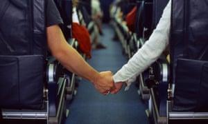 Couple holding hands across aisle of aeroplane