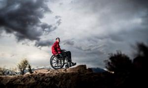 dramatic scene man in wheelchair on mountain