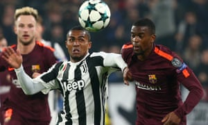 Juventus' Douglas Costa races Barcelona's Nelson Semedo for the ball.