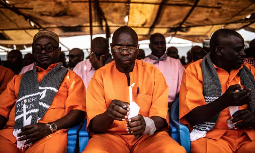 Inmates hold candles during a commemoration ceremony at Nyarugenge prison in Kigali