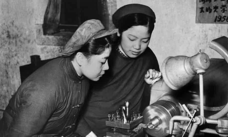 Two Chinese women in simple dark jackets, at their machines at a tool plant during the first decade of the People's Republic of China.