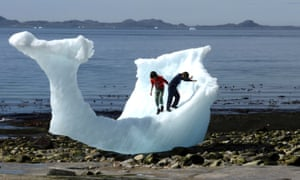 Children play amid icebergs on the beach in Nuuk, Greenland