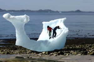 Children play on an iceberg on a beach in Nuuk, Greenland