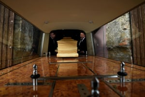 Funeral director and publican Jasper Murphy of McCarthy's Bar and Undertakers with his nephew Toby Collier load a prepared coffin into his hearse to collect the body of a deceased local man from hospital amid the coronavirus disease pandemic in the County Tipperary town of Fethard.