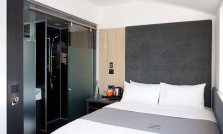 Bedroom, with shower unit in corner of room at Z Hotel Bath, Bath, UK.