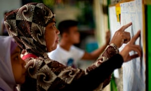 Muslim women look for their names at a voting precinct in Maguindanao, on the southern island of Mindanao. A decades-long push to halt the violence that has claimed some 150,000 lives in the southern Philippines culminates with a vote on giving the nation's Muslim minority greater control over the region.