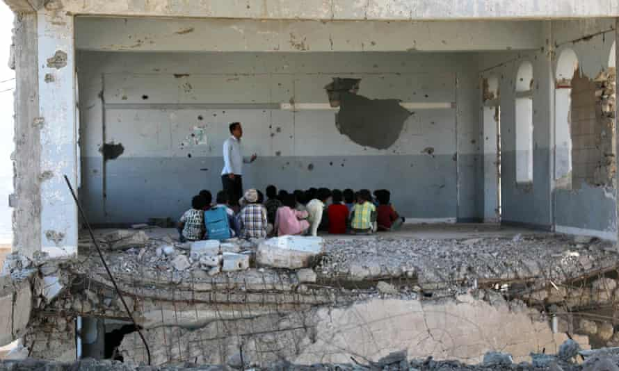 Yemeni children attend class in a bomb-damaged school in Taez on the first day of the new academic year on 3 September.