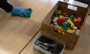 Early childhood educator Josephine wipes down tables and bench tops with disinfectant at the Robertson Street Kindy Childcare Centre in Helensburgh south of Sydney