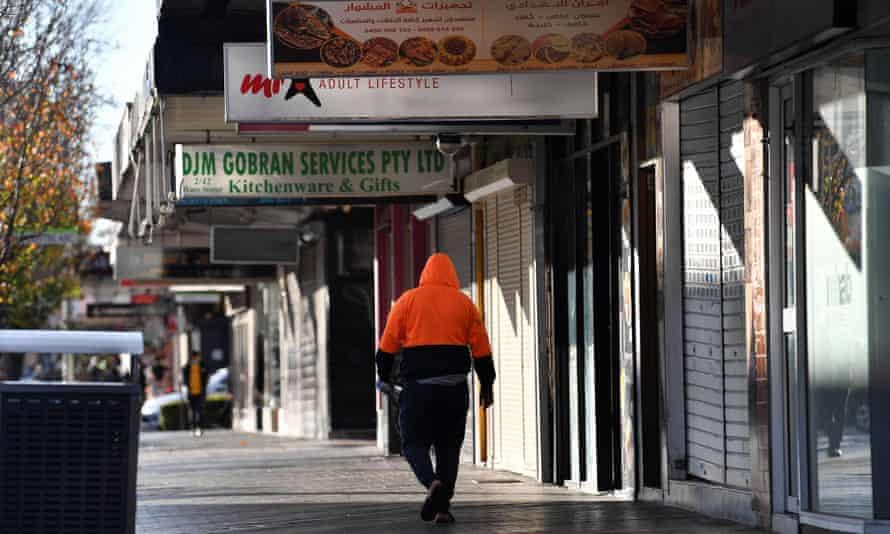 A man in high viz walks passed shuttered shops