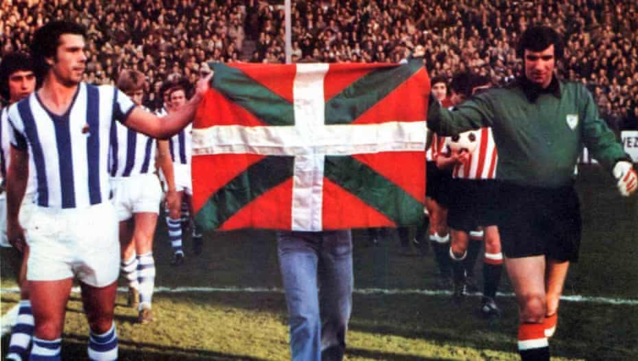 The captains Inaxio Kortabarría of Real Sociedad and José Ángel Iribar carry the still-illegal Basque flag before the derby in December 1976