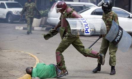 A Kenyan riot policeman kicks a protester after he fell running from them during a protest in May
