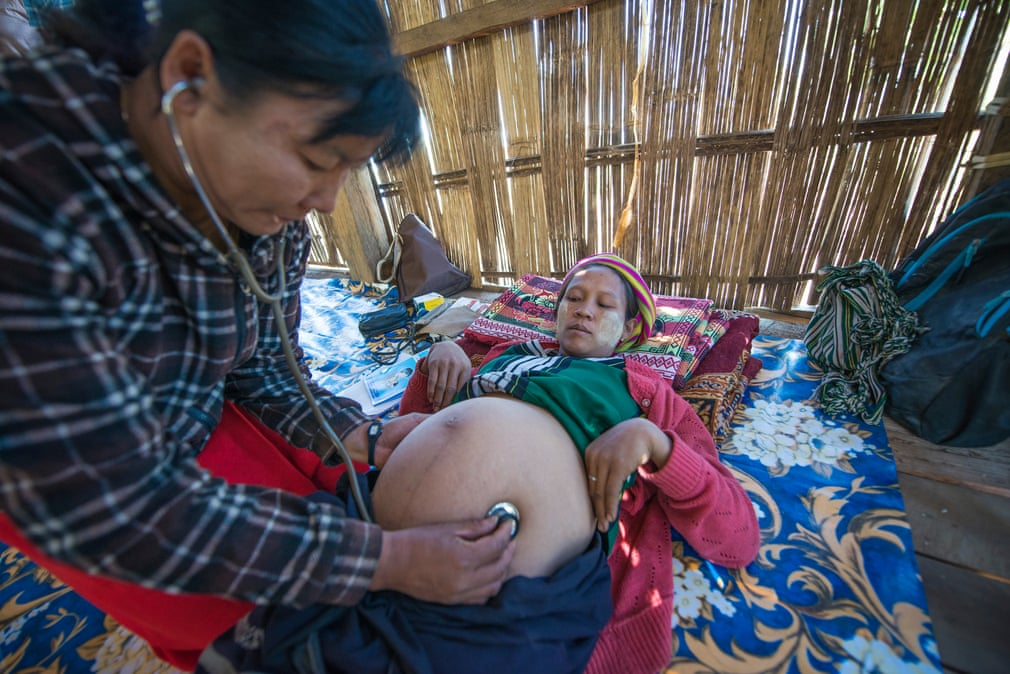 A midwife examines a heavily pregnant woman in Myanmar's Chin State