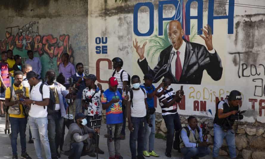 Journalists gather near a mural featuring President Jovenel Moïs.