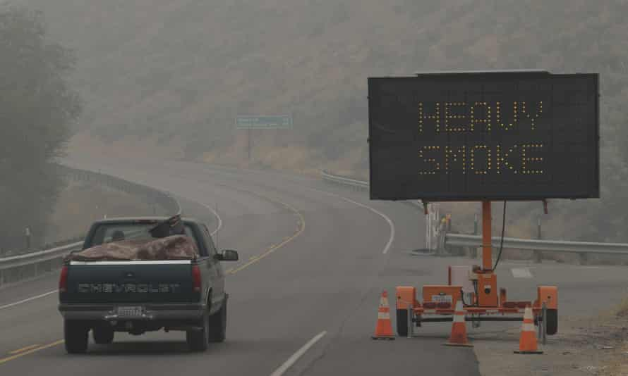 A sign warns of heavy smoke on Washington state route 155 near Omak, Wash., Wednesday, Aug. 26, 2015. Wildfires in the area have generated heavy smoke that has slowed traffic and in some instances hindered efforts to fight the fires from the air. (AP Photo/Ted S. Warren)