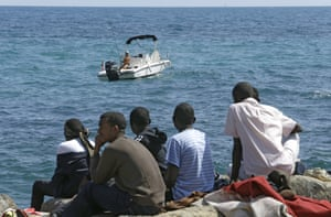 Migrants looks at a fisherman as they sit at the Franco-Italian border near Menton, south-eastern France.