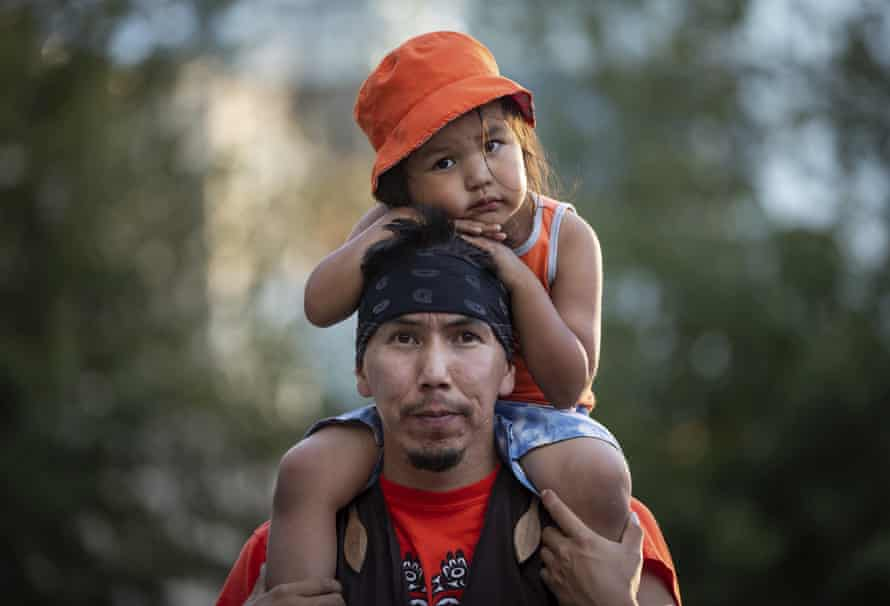 Cowichan tribe member Benny George holds his child Bowie, 3, on his shoulders as they listen during a ceremony and vigil for the 215 children whose remains were found buried at the former Kamloops Indian Residential School, in Vancouver, British Columbia