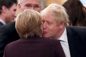 Angela Merkel and Boris Johnson greet each other during at Buckingham Palace