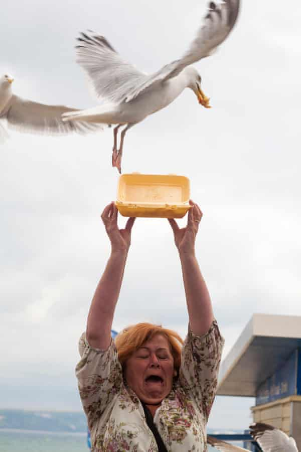 Woman holding leftover chips in polystyrene carton above her head to feed seagulls in Weymouth, Dorset.