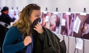 A woman covers her mouth in horror as she looks at a gruesome collection of images of dead bodies in Syria