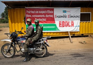 Congolese soldiers ride past sign warning of Ebola at entrance to Beni, DRC