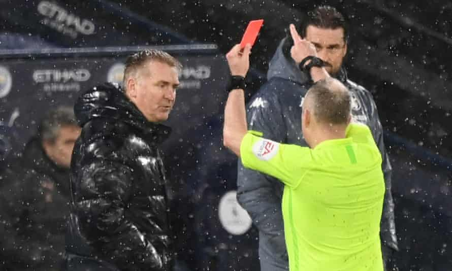 The Aston Villa manager, Dean Smith, is shown the red card by the referee in the pouring rain for protesting against Manchester City's first goal last week.