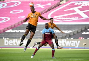 Wolves' Willy Boly heads clear as teammate Matt Doherty of and West Ham's Michail Antonio look on.