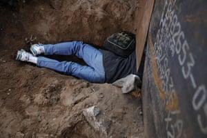 A Honduran migrant crawls through a hole under the US border fence in Tijuana, Mexico
