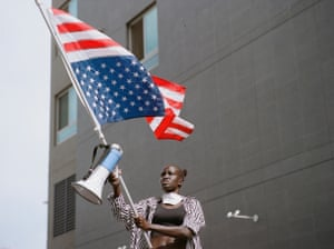 A young girl waves the US flag in front of a large grey building at a Black Lives Matter protest in Los Angeles, US, 2020