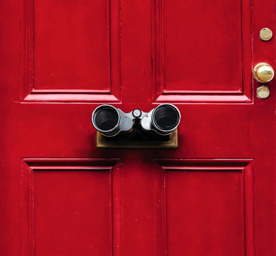 A red front door with binoculars sticking out of the letterbox