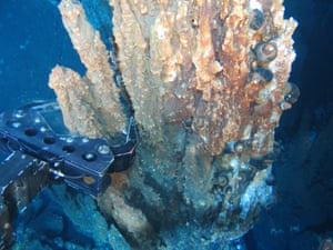 A robotic arm breaks off a chunk of mineral-rich rock for sampling deep underwater near Papua New Guinea.