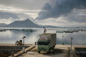 A man clears ash from the roof of his truck as steam rises from the Taal volcano in the Philippines