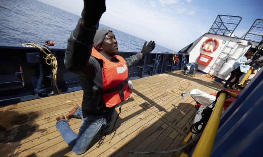 A man prays on the deck of the Sea-Watch humanitarian ship, Alan Kurdi