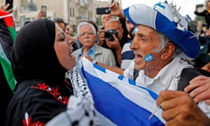 An Israeli man confronts a Palestinian woman at Damascus gate in Jerusalem on Sunday as Israeli settlers celebrate Jerusalem Day in the Old City