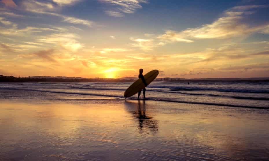 A person with a surfboard at sunset