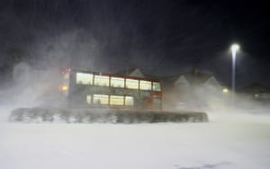 An early-morning bus passes through a snowstorm in Whitley Bay.