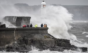 People watching waves crash against the harbour wall at Porthcawl, south Wales.