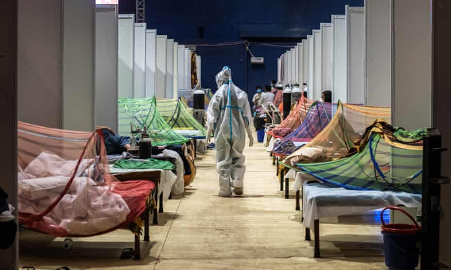A medical worker observes patients who have been infected by Covid-19 inside a makeshift are facility in a sports stadium in New Delhi on 2 May 2021.