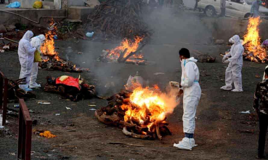Relatives wear protective equipment amid burning funeral pyres for Covid-19 victims in India.