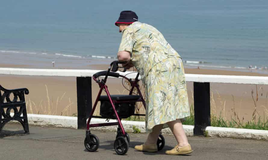 Older woman walking along the seafront with walking frame