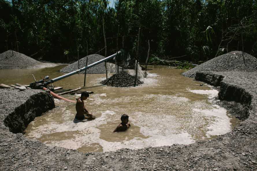 Illegal gold miners extract gold from sediment on the Marañón river